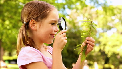 Little girl looking at plant through magnifying glass
