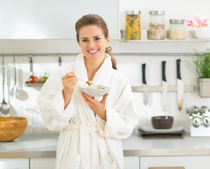 Portrait of smiling young woman eating muesli in kitchen