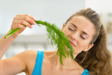 Portrait of young woman smelling fresh dill