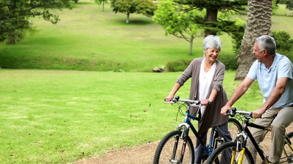 Retired couple in the park riding their bikes