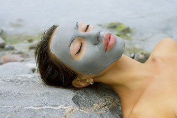 Woman with blue clay facial mask in beauty spa (wellness).