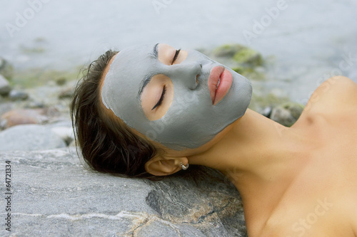 Leinwandbild Motiv Woman with blue clay facial mask in beauty spa (wellness).