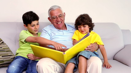 Senior man sitting on couch with his grandsons looking at photo