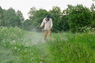 Worker man cut trim mow wet grass after rain