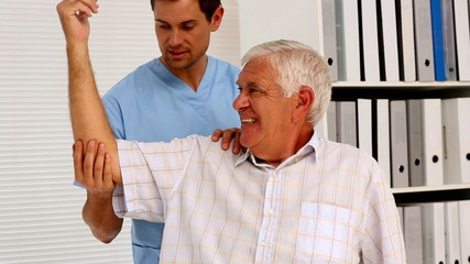 Male nurse showing elderly patient how to exercise his arm