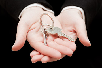 A real estate agent holding keys to a new house in her hands.