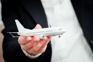 Business person holding airplane model. Transport, airline
