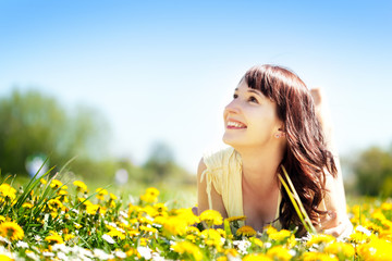 Young beautiful woman lying on grass in spring flowers, smiling