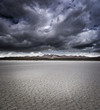 Dry lake bed with storm clouds - 64723574