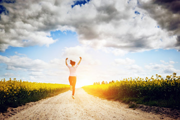 Happy young woman running and jumping for joy towards sun