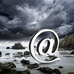 At symbol on a rocky beach