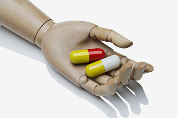 Large pills in an artist's manikin's hand