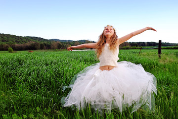 Cute girl with open arms in green grass field.