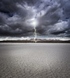 Dry lake bed with storm clouds and lightning - 64723955