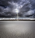 Dry lake bed with storm clouds and lightning