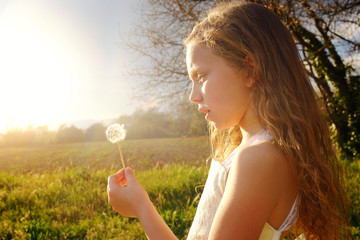 Girl holding dandelion at sunset.