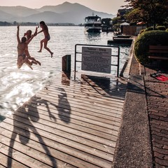 teenage girls jumping off a dock at lake