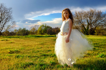Young girl wearing white dress in late afternoon sun.