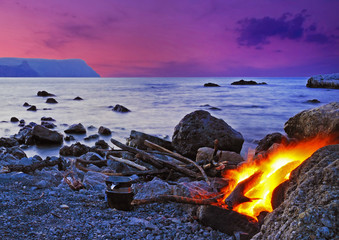 Wonderful landscape with bonfire on the seashore at sunset in Cr