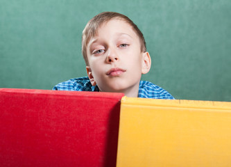 Cute funny bored boy sitting in classroom with books