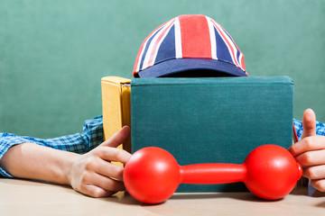 Funny British schoolboy with cap hiding behind books