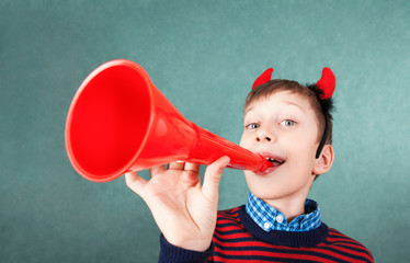 Funny naught boy as devil playing red pipe smiling