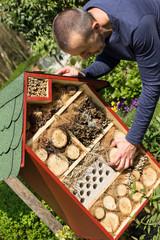 Mann an einem Insektenhaus