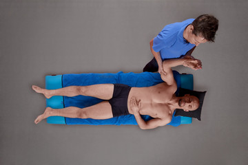 male therapist massaging muscular man's arm