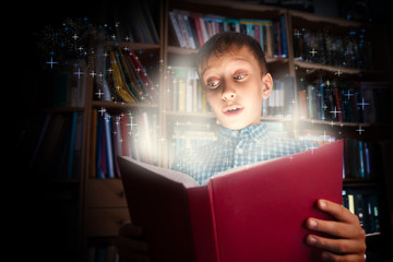 Beautiful funny child holds big book with magical light amazed
