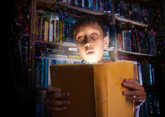 Funny child holding book with magic light amazed