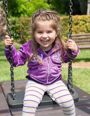 Bambina che gioca sull'altalena