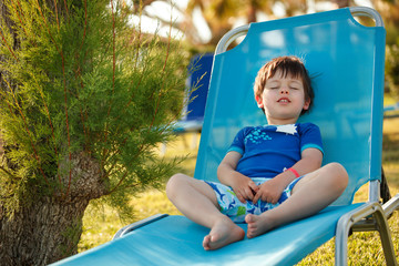 Cute toddler boy sitting on a sunbed