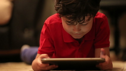 little cute kid using digital tablet in home
