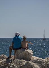 Padre con hijo sentados frente al mar