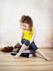 Pensive little girl sitting on the photo albums