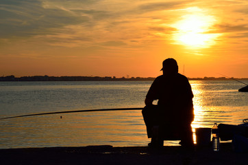 fisher on the pier at sunset