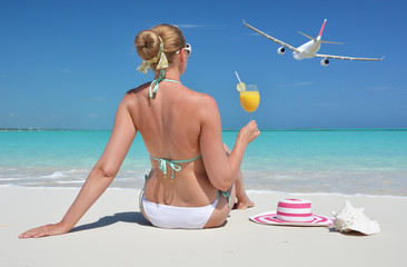 Girl with a glass of orange on the beach of Exuma, Bahamas