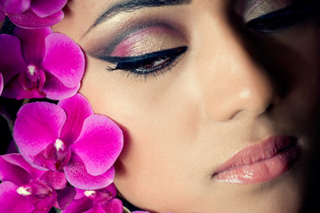 Closeup shot of a beautiful woman's face with orchids
