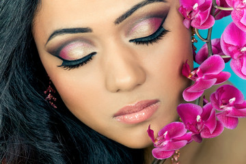 Closeup shot of a beautiful young woman's face with orchids