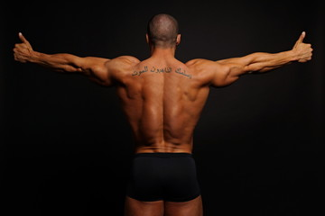 Muscular man with his arms outstretched showing his back