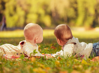 two baby boys looking away laying on a carpet at park grass