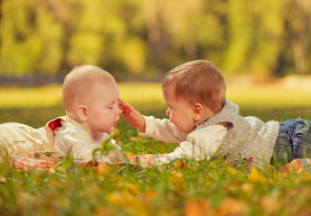 two babies on a fall park grass
