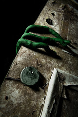 A green alien hand opening a scary, door.