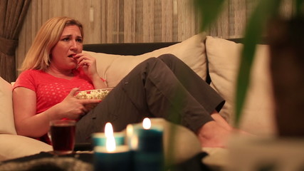 dolly shot blonde women eating popcorn and watching horror movie