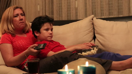 dolly shot mother and son eating popcorn and watching movie