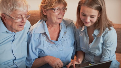 Young Girl and Old Person Learn Laptop
