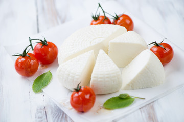 Sliced adygea cheese, baked cherry tomatoes and fresh mint