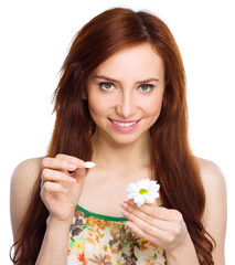 Young woman is tearing up daisy petals