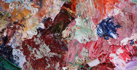 Abstract background mixing oil paints on a palette.