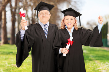 Mature couple celebrating their diplomas in park